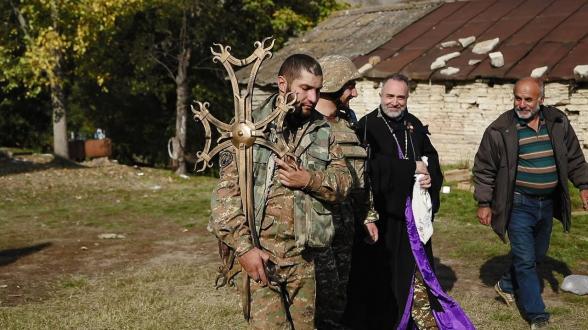 Հրետակոծության տակ զինվորականն ու հոգևորականը Արցախում տեղադրում են եկեղեցու խաչը